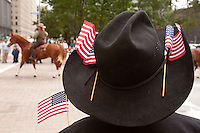 A spectator wearing a cowboy hat watches the 2015 Veteran's Day Parade in downtown Houston.