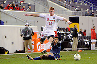 Tim Parker (18) of the St. John's Red Storm jumps over the tackle of Kevin Garcia (6) of the Villanova Wildcats. St. John's defeated Villanova 2-0 during the second semifinal match of the Big East Men's Soccer Championships at Red Bull Arena in Harrison, NJ, on November 11, 2011.