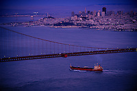 An oil tanker glides under San Francisco's Golden Gate Bridge. It is one of many ships in this busy port carrying, on the average a million gallons of water in ballast tanks, for stability in open waters. Large ships often carry 20 million gallons. In the past, water take up in a distant port was released here, devastating the <br /> ecosystem. California attempts to regulate the practice but it is still common here and in <br /> ports the world over,