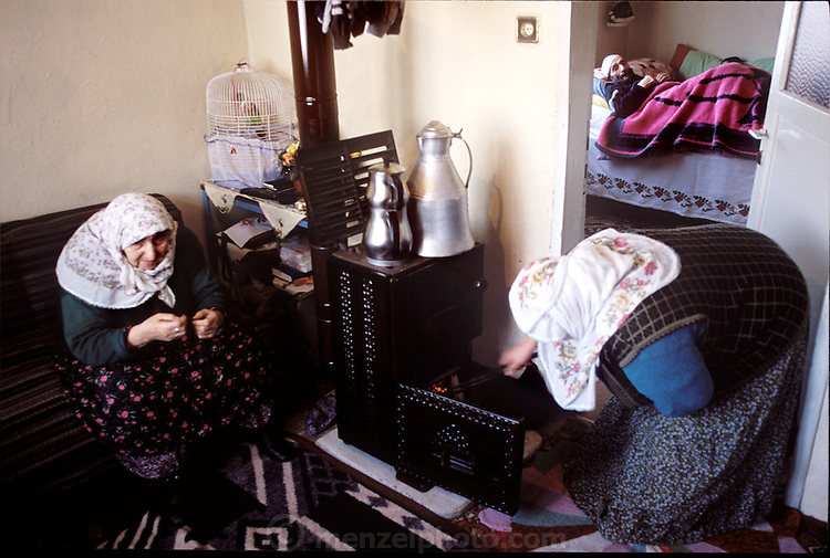 (MODEL RELEASED IMAGE). At their home in Golden Horn area of Istanbul, Turkey, Safiye Çinar strokes the fire for heat while her parents Emine (left) and Mehemet (lying on the bed in the other room) rest nearby. (Supporting image from the project Hungry Planet: What the World Eats.)