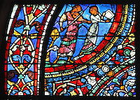 A man plays a viola and a woman carries a tray, accompanying the Reunion Feast, from the Parable of the Prodigal Son stained glass window, in the north transept of Chartres Cathedral, Eure-et-Loir, France. This window follows the parable as told by St Luke in his gospel. It is thought to have been donated by courtesans, who feature in 11 of the 30 sections. Chartres cathedral was built 1194-1250 and is a fine example of Gothic architecture. Most of its windows date from 1205-40 although a few earlier 12th century examples are also intact. It was declared a UNESCO World Heritage Site in 1979. Picture by Manuel Cohen