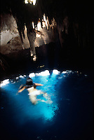Jasai swims in the cool natural waters of an underground cenote, rays of light from holes in the cenote´s roof shine through the water. Photos for Jasai´s catalogue of the houses of Memo and the surrounding area