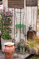 Rustic chair and old farm equipment, old bottles, flea market finds, antique chocolate molds, glass buoy, lantern, old buckets for container pots with ornamental grasses, hanging on wall for charming garden scene, climbing pink clematis vine need idin planter