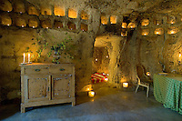 Niches cut in to the rough-hewn stone walls of the simply furnished living space of this grotto are filled with tealights