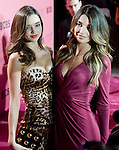 Victoria's Secret Angels Miranda Kerr, left, and Lily Aldridge pose for photos while waiting to do a live shot for CBS before the start of Tuesday's viewing party for the 2011 Victoria's Secret Fashion Show at the Samueli Theater at the Segerstrom Center for the Arts in Costa Mesa.
