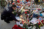 A Lakewood Police officer pays his respect to his fellow officers at a shrine of flowers, balloons, stuff animals, pictures and  wreaths that were left to form a makeshift memorial to four slain police officers at the Police Headquarters in Lakewood, Washington, USA, on 2 December  2009. Four Lakewood officers were gunned down during a morning meeting at a local coffee shop on 29 November 2009.  Jim Bryant Photo. ©2010. ALL RIGHTS RESERVED.
