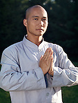 Portrait of a Shaolin warrior monk with hands folded in lotus, Amituofo, greeting or meditation position.
