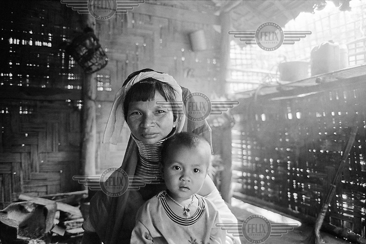 Kayan (Karenni) mother with one of her four daughters, in their kitchen.