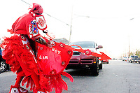 "Robert Stevenson, ""flag boy"" of the Golden Comanches Mardi Gras Indians, halts traffic by dancing in front of a car in New Orleans on February 28, 2006."