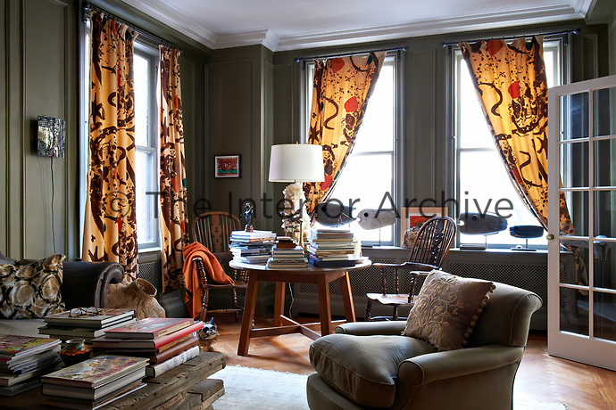 Yellow and brown 1940's patterned curtains by Alexander Calder make a bold statement against the sage green panelled library walls