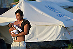 A man holds his two-month old child outside a tent where they live in Tacloban, a city in the Philippines province of Leyte that was hit hard by Typhoon Haiyan in November 2013. The storm was known locally as Yolanda. The ACT Alliance has been active here and in affected communities throughout the region helping survivors to rebuild their homes and recover their livelihoods.