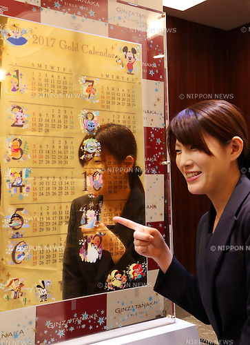 December 1, 2016, Tokyo, Japan - An employee of Japanese jeweler Tanaka Kikinzoku Jewelry displays a pure gold calendar for 2017 with Disney characters printed at the company's Ginza shop in Tokyo on Thursday, December 1, 2016. The calendar measuring 72cm x 45cm and weighing 12.5 kilograms is priced at 125 million yen (1.25 million US dollars) while small one is 5 gram and priced 50,000 yen (500 US dollars).   (Photo by Yoshio Tsunoda/AFLO) LWX -ytd-