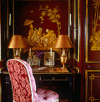 A small writing table fits into an alcove in the red-lacquered panelling of the Chinese boudoir
