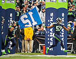 Seattle Seahawks linebacker Michael Morgan (57) leads the teams onto the field while displaying the12th Man flag before their game against the Arizona Cardinals at CenturyLink Field in Seattle, Washington on November 23, 2014. The Seahawks beat the Cardinals 19-3.   ©2014. Jim Bryant Photo. All Rights Reserved.
