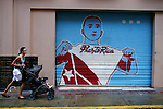 A woman pushes a stroller past a mural of a baseball player, in San Juan, Puerto Rico, on Friday, November 14, 2008.
