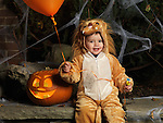 Baby boy in a Halloween costume with a balloon and candy sitting beside a carved pumpkin