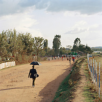 Man walking down a street under a sun shade umbrella in Lalibela, Ethiopia