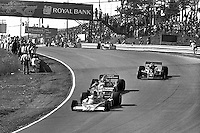 BOWMANVILLE, ONTARIO - OCTOBER 3: James Hunt of Great Britain drives his McLaren M23 8-2/Ford Cosworth ahead of a group of cars en route to winning the Canadian Grand Prix FIA Formula 1 race at Mosport Park near Bowmanville, Ontario, on October 3, 1976.