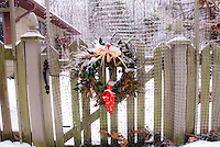 Holiday Wreath in winter snow and ice, hanging on gate of picket fence