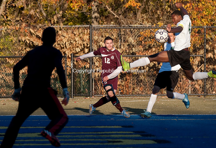 WATERBURY, CT--- -102615JS08---Wilby's Rohan Rhule (4) tries to clear a centering pass by Torrington's Dalton Finello (12) as Wilby goalkeeper Christian Colon looks on during their game Monday at Municipal Stadium in Waterbury. <br />  Jim Shannon Republican-American