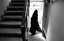A girl in black chador is leaving the Omid-e-Merh daycenter for runaway  and troubled children is leaving the center after a day of classes and workshops. This shelter gives psychological and practical help to young girls from troubled backgrounds. Tehran, Iran, 2007
