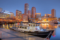 The Outward Bound Thompson Island Ferry sits moored in front of the skyline in the last hour before sunrise as a new day begins in Boston, Massachusetts.