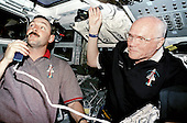 STS-95 mission Commander Curtis Brown (left) and Payload Specialist John Glenn are photographed on the aft flight deck of Discovery during a press conference from Earth orbit on November 1, 1998..Credit: NASA via CNP