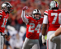 Ohio State Buckeyes kicker Drew Basil (24) hugs Ohio State Buckeyes offensive linesman Darryl Baldwin (76) after kicking a point after during the first half of the NCAA football game at Ohio Stadium in Columbus on Oct. 26, 2013. (Adam Cairns / The Columbus Dispatch)