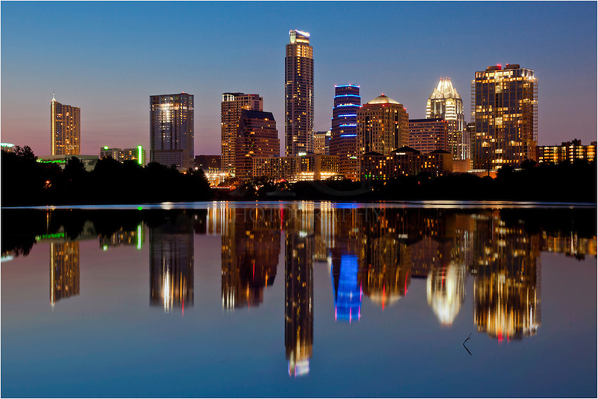 On a summer evening, the highrises of Austin, Texas, are reflected on a still and calm Lady Bird Lake.