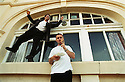DAMIEN HIRST SMOKES A CHIP WHILST BUSINESS PARTNER SIMON BROWNE DANCES ON THE WINDOW SILL TO CELEBRATE THE PURCHASE OF THE QUAY, ILFRACOMBE, WHICH THEY PLAN TO TURN INTO A RESTAURANT.