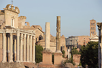 Temple of Antoninus and Faustina, 141 AD, transformed in the Christian era into the church of San Lorenzo In Miranda remaining the façade with the colossal columns in Euboeian marble, Santa Francesca Romana and Colosseum in the distance, Roman Forum, Rome, Italy, Europe.