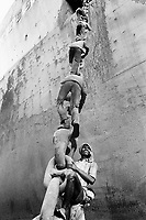 India. Province of Gujarat. Alang. Workers, all men, climb up the anchor's chain to have access to the boat. Bottom of ship. Ships aground. Vessels stranded. Alang, located in the Gulf of Khambhat, is a ships breaking place. Alang is considered as the biggest scrapyard in the world. Ships recycling for its metals. Environmental issues. Hazardous waste. © 1992 Didier Ruef