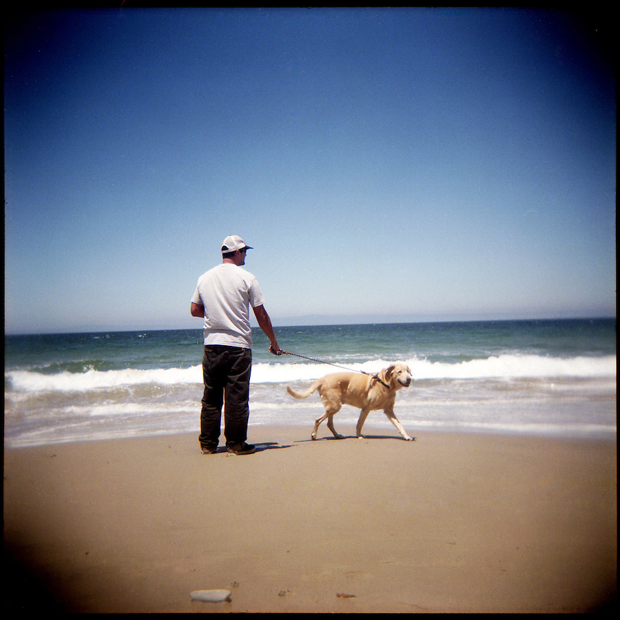 George Rocha, and his dog, Reese, of San Francisco, walk along the beach, in Monterey, Ca., on Wednesday, July 14, 2010.