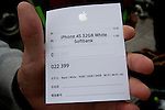 A ticket for the pre-ordering of the new iphone 4S in the hands of someone in the lines of people at the Apple store awaiting the official release of the iphone4S in Ginza, Tokyo, Japan. Friday October 14th 2011. The latest version of the popular iphone was released worldwide on October 14th. Japans flagship Apple store in Ginza was opened at 8am for the 800 people that had been waiting to be the first to purchase the new telephone.