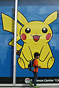 May 9, 2010 - Tokyo, Japan - A young Japanese boy walks past a poster featuring a video game Nintendo's Pokemon character at the official Pokemon store in Tokyo on May 9, 2010. Nintendo recently announced that the DS handheld device had become the best selling gaming handheld of all time, with a total of 129 million units sold. The DS 'family' have surpassed the &quot;Game Boy&quot; series which hit 118 million over two decades.