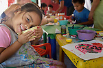 Evelyn Garcia Aguilar poses as she creates a painting during an arts and crafts session of the early intervention program of Piña Palmera, a center for community based rehabilitation for people living with disabilities in Zipolite, a town in Oaxaca, Mexico. The 4-year old girl is deaf.