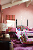 The girl's bedroom is a palette of pinks set off by a riot of colour and pattern in the bedding and soft furnishings