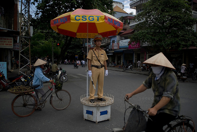 A Vietnamese police officer directs traffic in Hanoi, Vietnam.