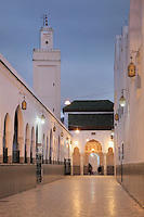 Evening view of the access corridor to the Mausoleum of Moulay Idriss I, running alongside a courtyard (through the horseshoe arches) and with the minaret above, Moulay Idriss, Meknes-Tafilalet, Northern Morocco. The mausoleum was rebuilt by Moulay Ismail, 1672-1727, in the 17th century and is the site of an important moussem or pilgrimage festival each summer. The town was founded by Moulay Idriss I, who arrived in 789 AD and ruled until 791, bringing Islam to Morocco and founding the Idrisid Dynasty. His body was moved to a tomb in the mausoleum. Picture by Manuel Cohen