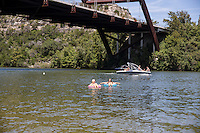 Ski boats pass as two beautiful women relax and suntan while floating inner tubes on Lake Austin at the Loop 360 Bridge Park Beach in Austin, Texas.