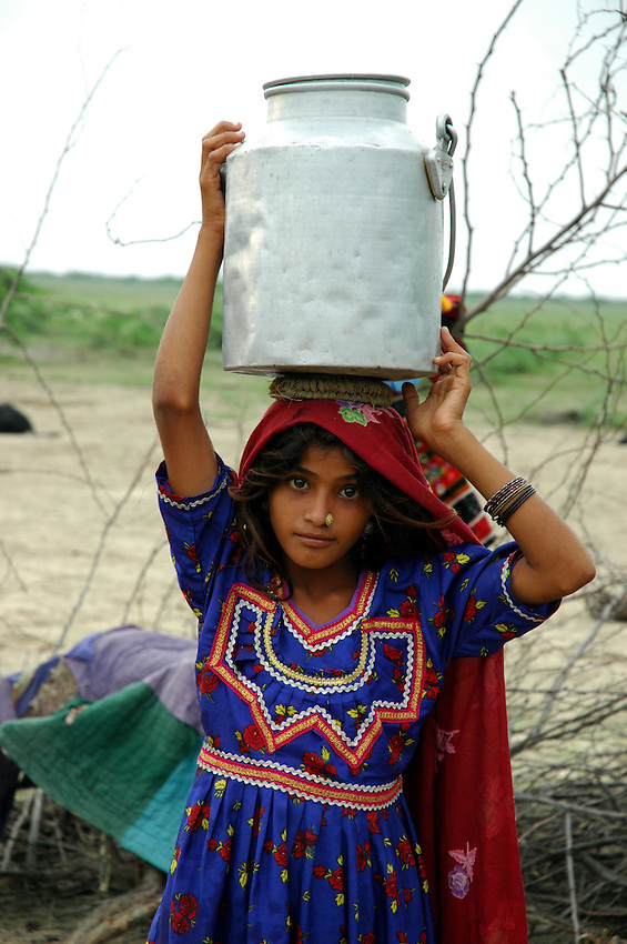 A Muslim Maldhari girl carries water to her nomad camp...by Michael Benanav - mbenanav@gmail.com