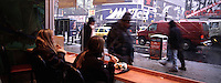 """Out takes from """"The Harvard Design School Guide to Shopping"""" published by Tashen. Two women eat at the times square Mc Donalds and watch the activity on the busy streets. NY 2000"""
