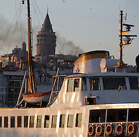 Ferry arriving at Eminonu with the Galata Tower in the distance, Istanbul, Marmara, Turkey. Eminonu is on the South bank of the Golden Horn at the Southern end of the Galata bridge. The Galata Tower or Galata Kulesi was built in 1348 during an expansion of the Genoese colony in Constantinople, as part of the fortifications of its citadel. Today it houses a restaurant, cafe and nightclub. Picture by Manuel Cohen