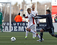 New England Revolution midfielder Scott Caldwell (6) dribbles as Sporting Kansas City forward Claudio Bieler (16) defends.  In a Major League Soccer (MLS) match, Sporting Kansas City (blue) tied the New England Revolution (white), 0-0, at Gillette Stadium on March 23, 2013.