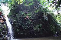 Local jumping into pool at jungle waterfall, Maunawili Trail, Kailua, Oahu. Hawaii