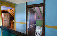 The two bedrooms are glimpsed open doors on the landing which has been painted a vibrant turquoise with woodwork in a contrasting yellow ochre