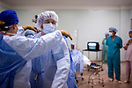 Estelle Raath, of South Africa, dresses Dr. James Brandt, of Sacramento, in a sterilized gown before performing surgery on a glaucoma patient at the Ho Chi Minh City Eye Hospital on Thursday, April 17, 2008.  Kevin German /  kevin@kevingerman.com..ORBIS Flying Eye Hospital brought doctors, nurses and specialists from all over the world to Ho Chi Minh City, Vietnam from April 7-18, 2008.  The ORBIS program contributed to the efforts of Ho Chi Minh City Eye Hospital in fighting avoidable blindness by educating local ophthalmologists to diagnose and manage pediatric blindness, retinal disease, oculoplastics, and blindness due to glaucoma...