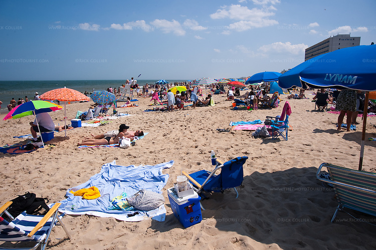 Absent beachgoers have staked out prime real estate amid sunbathers on the beach at Rehoboth Beach, Delaware, USA.