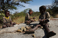 Yaeda Valley, Tanzania: Millie, Yaeda, and Gody, Hadzabe children, at work in the hills surrounding this valley in Northern Tanzania. The Hadzabe are the second oldest people on Earth, and one of the last remaining tribes of hunter gatherers, with a culture dating back at least 60,000 years. Here, the children smash fruits they collected earlier from a baobab tree, and grind the seeds and pulp into a flour they eat. (PHOTO: MIGUEL JUAREZ LUGO)
