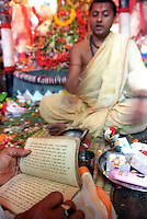 INDIA (West Bengal - Calcutta)  2006, A priest chants from a religious sanskrit book as a form of worship of Durga.  Durga Puja Festival is the biggest festival among bengalies.  As Calcutta is the capital of West Bengal and cultural hub of  the bengali community Durga puja is held with the maximum pomp and vigour. Ritualistic worship, food, drink, new clothes, visiting friends and relatives places and merryment is a part of it. In this festival the hindus worship a ten handed godess riding on a lion armed wth all possible deadly ancient weapons along with her 4 children (Ganesha - God for sucess, Saraswati - Goddess for arts and education, Laxmi - Goddess of wealth and prosperity, Kartikeya - The god of manly hood and beauty). Durga is symbolised as the women power in Indian Mythology.  In Calcutta people from all the religions enjoy these four days of festival in the moth of October. Now the religious festival has become the biggest cultural extravagenza of Calcutta the cultural capital of India. Artistry and craftsmanship can be seen in different sizes and shapes in form of the idol, the interior decor and as well as the pandals erected on the streets, roads and  parks.- Arindam Mukherjee